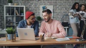 Hombres jovenes que discuten el proyecto que mira la pantalla del ordenador portátil en oficina moderna creativa almacen de metraje de vídeo