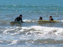 Hombres jovenes que ejercitan en practicar surf en los tableros Fotos de archivo