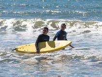 Hombres jovenes que ejercitan en practicar surf en los tableros Imagen de archivo