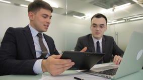 Hombres jovenes que hablan, usando el ordenador portátil y la tableta en compañía grande almacen de metraje de vídeo