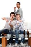 Hombres jovenes que juegan los juegos de ordenador Foto de archivo