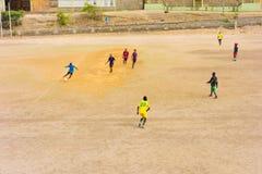 Hombres jovenes que juegan a un juego casual del fútbol en un campo seco en las zonas tropicales Fotos de archivo