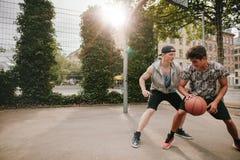 Hombres jovenes que juegan a un juego del baloncesto Fotos de archivo
