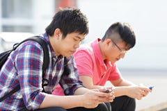 Hombres jovenes que miran en el teléfono celular Foto de archivo libre de regalías