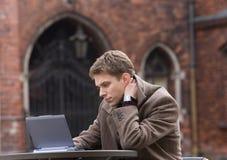 Hombres jovenes que piensan cerca de la computadora portátil Fotos de archivo libres de regalías
