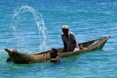 Hombres jovenes que salpican el agua del boatin Madagascar Fotos de archivo