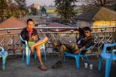 Hombres jovenes que se relajan en la cafetería en puesta del sol Imágenes de archivo libres de regalías