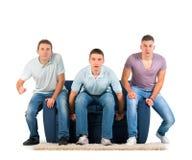 Hombres jovenes que se sientan en un sofá que anticipa Foto de archivo libre de regalías