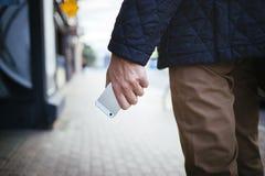 Hombres jovenes que sostienen smartphone disponible en la calle Imagen de archivo libre de regalías