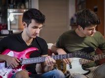 Hombres jovenes que tocan las guitarras eléctricas Fotos de archivo