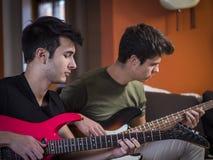 Hombres jovenes que tocan las guitarras eléctricas Imágenes de archivo libres de regalías