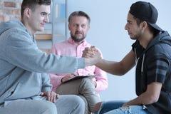 Hombres jovenes reconciliados durante terapia con el consejero para el rebelliou fotografía de archivo