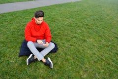 Hombres jovenes usando la tableta digital en parque público imagenes de archivo