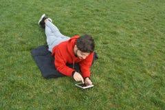 Hombres jovenes usando la tableta digital en parque público fotos de archivo