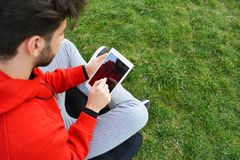 Hombres jovenes usando la tableta digital en parque público imagen de archivo