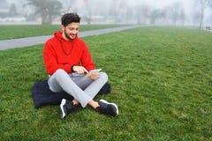 Hombres jovenes usando la tableta digital en parque público fotos de archivo libres de regalías