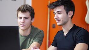 Hombres jovenes videochatting en la PC del ordenador portátil