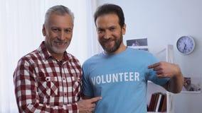 Hombres jovenes y mayores que muestran la palabra voluntaria en la camiseta a la c?mara, caridad almacen de video
