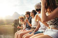 Hombres jovenes y mujer que se sientan en el embarcadero con las cervezas Foto de archivo