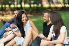 Hombres jovenes y mujeres alegres que hablan en parque Fotos de archivo