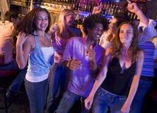 Hombres jovenes y mujeres que bailan en un club nocturno Imagen de archivo