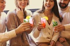 Hombres jovenes y mujeres que beben el cóctel en el partido fotografía de archivo