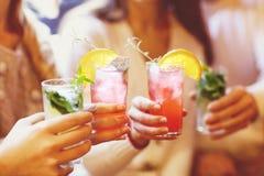 Hombres jovenes y mujeres que beben el cóctel en el partido fotografía de archivo libre de regalías