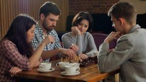 Hombres jovenes y mujeres que juegan a ajedrez Imagenes de archivo