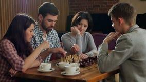 Hombres jovenes y mujeres que juegan a ajedrez metrajes