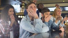 Hombres jovenes y mujeres que miran campeonato del deporte el parecer infeliz, pérdida del equipo almacen de video
