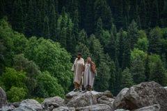 Hombres locales que se colocan en roca con el bosque del ?rbol de pino foto de archivo libre de regalías