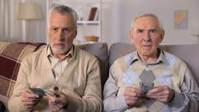Hombres mayores descontentados que cuentan los dólares, pago social bajo, problemas de la pobreza almacen de metraje de vídeo