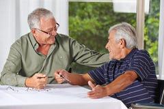 Hombres mayores felices que solucionan el crucigrama Imagen de archivo libre de regalías