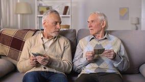 Hombres mayores presionados que cuentan el dinero, pago social bajo, problemas de la pobreza almacen de video
