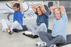 Hombres mayores que estiran en aptitud fotos de archivo