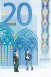 Hombres miniatura que dan un paseo con el cierre del fondo del billete de banco del euro 20 para arriba Imágenes de archivo libres de regalías