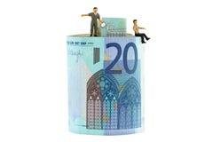 2 hombres miniatura que se colocan y que se sientan en un rollo del billete de banco euro Fotos de archivo