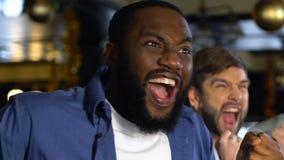 Hombres multiétnicos que animan para el partido que gana del equipo de deportes, celebrando meta en pub almacen de metraje de vídeo