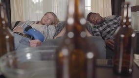 Hombres multiculturales del retrato que duermen en el sofá después de mirar el boxeo en la TV Las botellas y los microprocesado metrajes