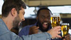 Hombres multirraciales emocionados que tintinean los vidrios de cerveza, juego de observación del deporte en pub metrajes