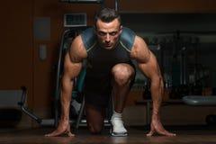 Hombres musculares fuertes que se arrodillan en el piso Imagen de archivo