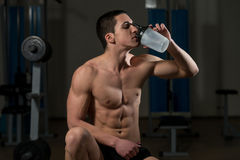 Hombres musculares jovenes que beben una botella de agua Fotografía de archivo libre de regalías