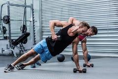 Hombres musculares que hacen un tablón lateral Foto de archivo libre de regalías