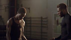 Hombres negros atléticos que se resuelven en gimnasio junto almacen de video