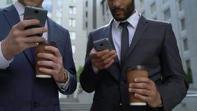 Hombres ocupados que comprueban noticias en smartphones en el descanso para tomar café, empleo 24 horas al día almacen de video