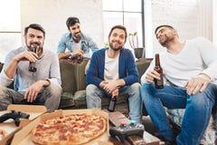 Hombres positivos alegres que descansan en casa Foto de archivo