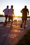 Hombres que activan en la playa en la puesta del sol Fotos de archivo