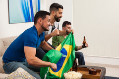 Hombres que animan con una bandera brasileña Fotos de archivo libres de regalías