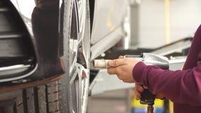 Hombres que atornillan la rueda de coche en el garaje metrajes