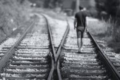 Hombres que caminan abajo de las pistas ferroviarias Imagenes de archivo
